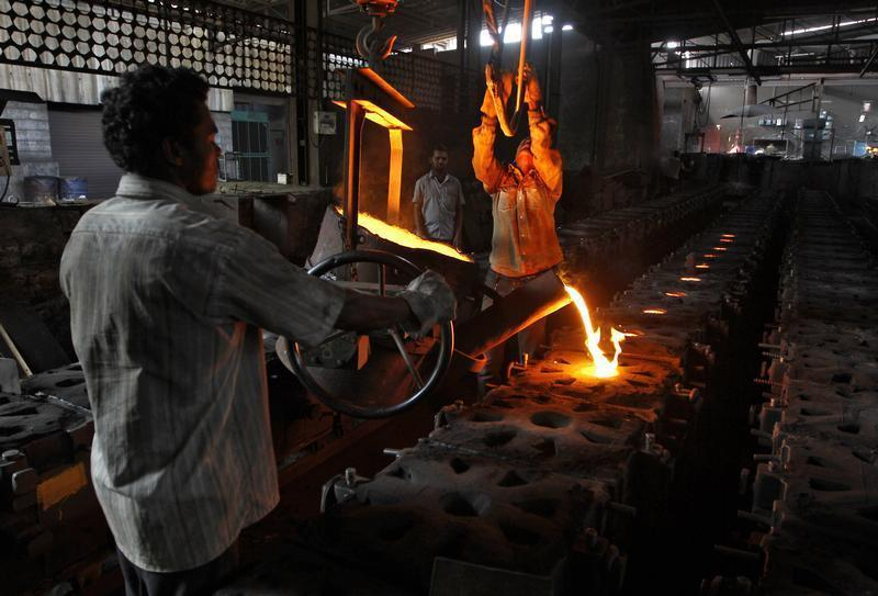 Workers tend to a furnace at a steel factory in the outskirts of Coimbatore
