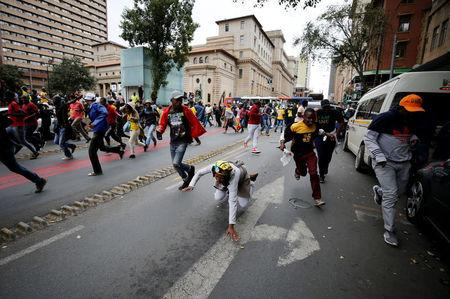 Supporters of the African National Congress (ANC) and South Africa's President Jacob Zuma flee from police in Johannesburg