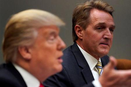FILE PHOTO: U.S. President Donald Trump, flanked by U.S. Senator Jeff Flake, speaks to reporters prior to a lunch meeting with Senate Republicans at the White House in Washington, DC, U.S., December 5, 2017.  REUTERS/Jonathan Ernst/File Photo