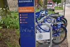 Bikes in a bike share are seen on a rack.