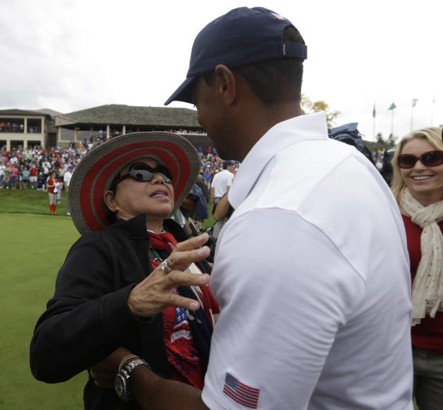United States team player Tiger Woods, right, gets a hug from his mother Kultida Woods on the 18th green during the single matches at the Presidents Cup golf tournament at Muirfield Village Golf Club Sunday, Oct. 6, 2013, in Dublin, Ohio. (AP Photo/Darron Cummings)