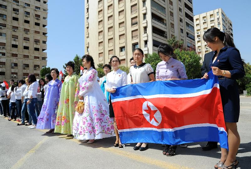 Young women hold a North-Korean flag during a ceremony to name a park in Damascus, Syria after Kim Il-sung, the late founder and supreme leader of the Democratic People's Republic of Korea (DPRK), on August 31, 2015