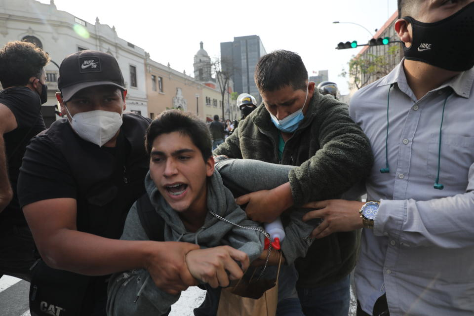 Plainclothes policemen detain a supporter of ousted President Martin Vizcarra near a police barricade, preventing marchers who are refusing to recognize the new government from reaching Congress, in Lima, Peru, Wednesday, Nov. 11, 2020. On Tuesday, Peru swore in Manuel Merino as president, after Peru's legislature booted Vizcarra from office on Monday. (AP Photo/Rodrigo Abd)