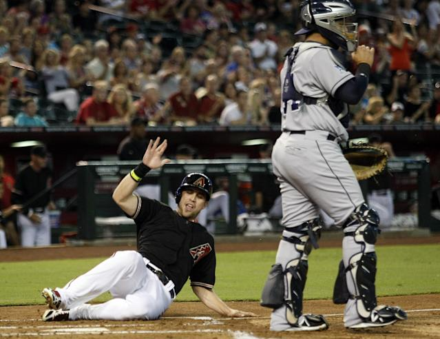 Arizona Diamondbacks' Ender Inciarte, left, scores past San Diego Padres catcher Rene Rivera in the first inning of a baseball game, Saturday, Aug. 23, 2014, in Phoenix. (AP Photo/Rick Scuteri)