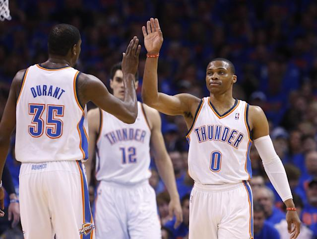 Oklahoma City Thunder guard Russell Westbrook (0) high-fives teammate Kevin Durant (35) in the first quarter of Game 7 of an opening-round NBA basketball playoff series against the Memphis Grizzlies in Oklahoma City, Saturday, May 3, 2014. (AP Photo/Sue Ogrocki)