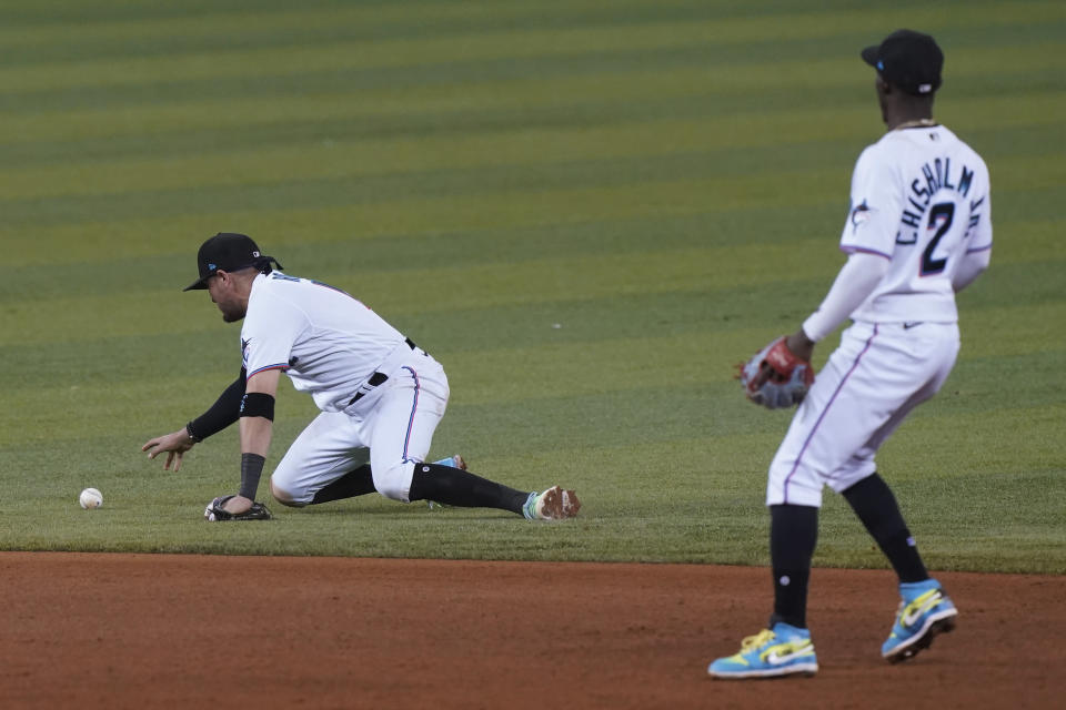 Miami Marlins shortstop Miguel Rojas (19) reaches for the ball after dropping the catch on a hit by Washington Nationals Luis Garcia during the sixth inning of a baseball game, Tuesday, Sept. 21, 2021, in Miami. To the right is Miami Marlins' second baseman Jazz Chisholm Jr. (2). (AP Photo/Marta Lavandier)