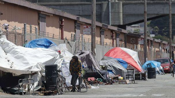 PHOTO: This Thursday, June 27, 2019, file photo shows a man holding a bicycle tire outside of a tent along a street in San Francisco. (Jeff Chiu/AP, FILE)