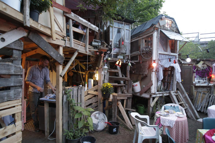 """British set designer Tony Hornecker prepares dinner at his restaurant """"The Pale Blue Door"""" in Berlin, September 12, 2010. A British set designer has taken his love for art, added some food, and opened a temporary pop-up restaurant -- made with scrap materials scavenged from the streets -- in one of Berlin's central community gardens. Tony Hornecker, the mastermind behind the thriving shanty town-style restaurant """"The Pale Blue Door"""", said that he does not make any profits with his fanciful underground restaurant, but feels that he is giving Berlin a unique attraction. REUTERS/Tobias Schwarz"""