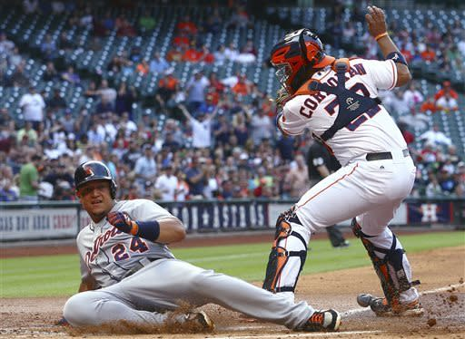 Detroit Tigers' Miguel Cabrera (24) slides safely into home against Houston Astros catcher Carlos Corporan (22) during the first inning of a baseball game Saturday, May 4, 2013, in Houston. (AP Photo/Patric Schneider)