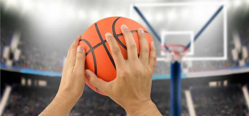 Hands hold a basketball to shoot it.