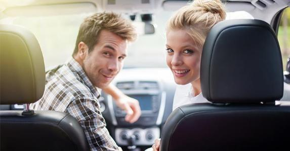 Couple seated in front seat of car, looking back copyright Jack Frog/Shutterstock.com
