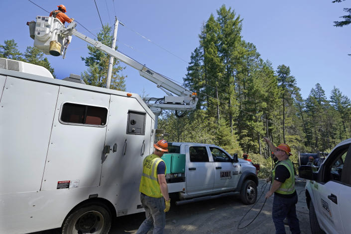 FILE - In this Wednesday, Aug. 4, 2021, file photo, workers with the Mason County (Wash.) Public Utility District install fiber optic cable, as part of a project to bring broadband internet service to homes in a rural area surrounding Lake Christine near Belfair, Wash. (AP Photo/Ted S. Warren, File)