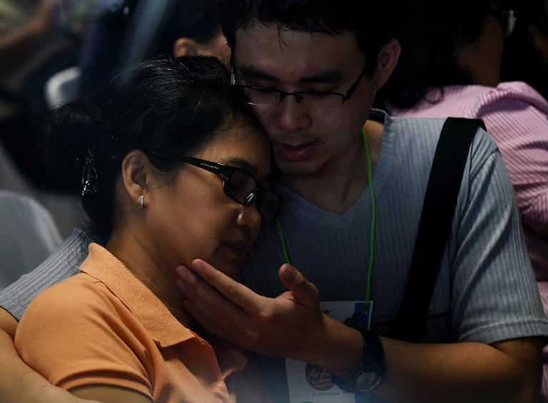 Family members of passengers onboard AirAsia Flight QZ8501 react to news about the discovery of debris found floating in the search area, inside the crisis-centre set up at Juanda International Airport in Surabaya