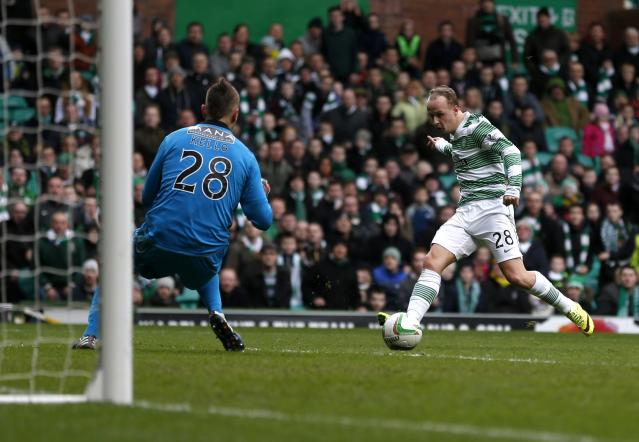 Celtic's Leigh Griffiths puts the ball past St Mirren goalkeeper Marian Kello to score during their Scottish Premier League soccer match at Celtic Park Stadium in Glasgow, Scotland March 22, 2014. REUTERS/Russell Cheyne (BRITAIN - Tags: SPORT SOCCER)