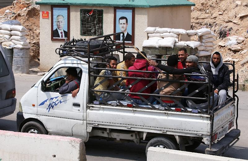 A vehicle carrying Jaish al-Islam fighters and their family members evacuated from the Eastern Ghouta town of Douma, arrives at the Wafideen Camp on April 12, 2018 (AFP Photo/Youssef KARWASHAN)