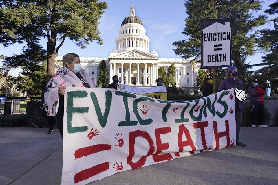 Demonstrators gather in front of the capitol building in Sacramento, California, holding a sign saying