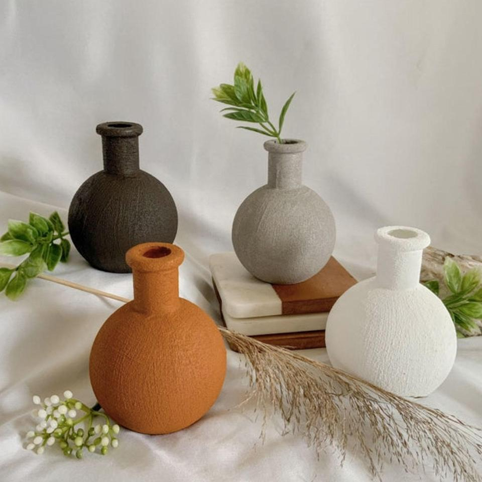 """These small vases are hand-painted with a matte, chalky texture to mimic ceramic pottery for a clay effect. The four neutral hues make them a versatile pick that will put an earthy, modern spin on your space—and give little stems and mini blooms a tasteful home. $12, Etsy. <a href=""""https://www.etsy.com/listing/872643553/mini-hand-painted-vase"""" rel=""""nofollow noopener"""" target=""""_blank"""" data-ylk=""""slk:Get it now!"""" class=""""link rapid-noclick-resp"""">Get it now!</a>"""