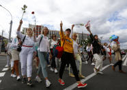 "Belarusian women carry flowers on a rally in solidarity with protesters injured in the latest rallies against the results of the country's presidential election in Minsk, Belarus, Thursday, Aug. 13, 2020. Hundreds of people were back on the streets of Belarus' capital on Thursday morning, forming long ""lines of solidarity"" in protest against an election they say was rigged to extend the rule of the country's authoritarian leader and against a crackdown on rallies that followed the vote. (AP Photo/Sergei Grits)"