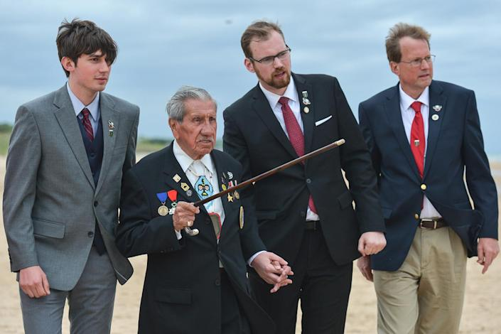 """<p>It was 73 years ago when Army Medic Edward """"Eddie"""" Morozewicz lost his life on D-Day, as part of the Allied forces landing on Omaha Beach in Normandy, France. (L-R) Kevin Weinpel (great nephew of Eddie), Charles Norman Shay (age 92), a Native American D-Day veteran-soldier, Jason Weinpel (great nephew of Eddie) and Phil Weinpel (nephew of Eddie), walk on Omaha beach, just hours ahead the 73rd anniversary of D-Day.<br> (Photo: Artur Widak/NurPhoto via Getty Images) </p>"""