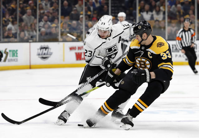 Boston Bruins' Zdeno Chara (33) battles Los Angeles Kings' Dustin Brown for the puck during the first period of an NHL hockey game Saturday, Feb. 9, 2019, in Boston. (AP Photo/Winslow Townson)