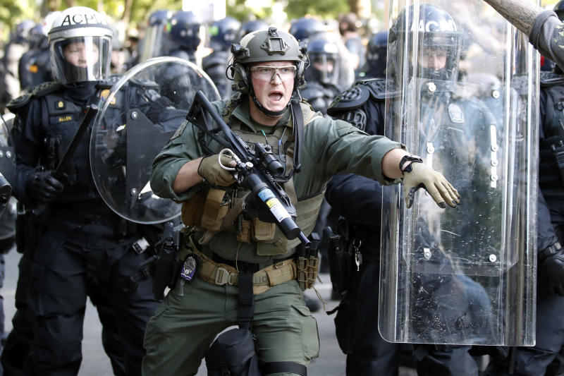 Police begin to clear demonstrators gathered as they protest the death of George Floyd, Monday, June 1, 2020, near the White House in Washington. Floyd died after being restrained by Minneapolis police officers. (AP Photo/Alex Brandon)