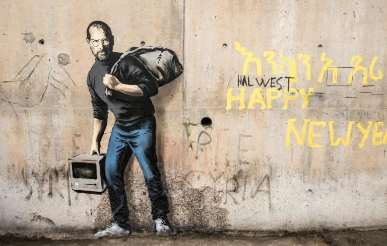 """Banksy often produces art in charged political settings, such as this 2015 mural in the Calais """"jungle"""" of migrants seeking to leave France for Britain, entitled """"The Son of a Migrant from Syria"""" and depicting Apple co-founder Steve Jobs, who was of Syrian descent"""