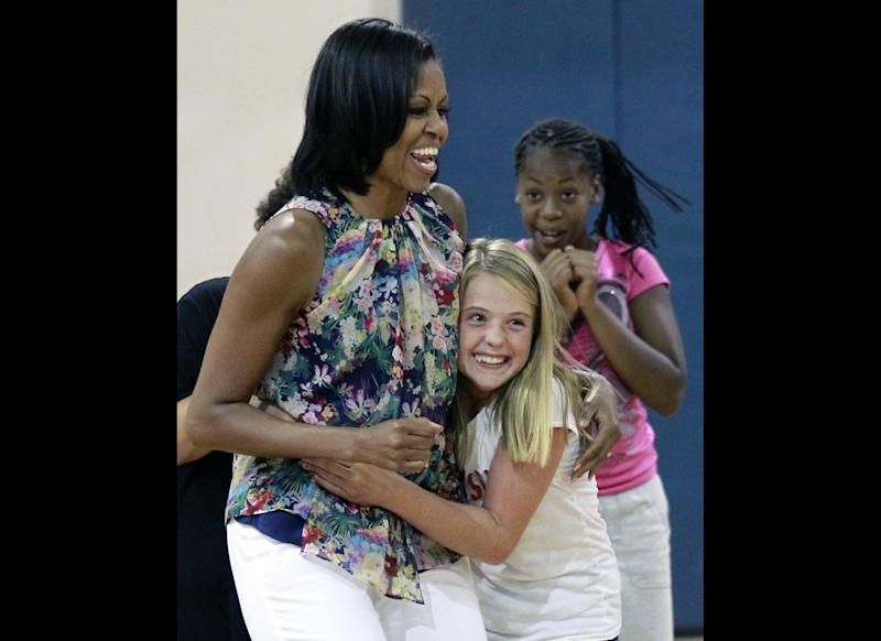 First lady Michelle Obama, left, gets a hug from Savannah Southerland during a children's fitness class on a suprise visit to the Blanchard Park YMCA, Tuesday, July 10, 2012, in Orlando, Fla.