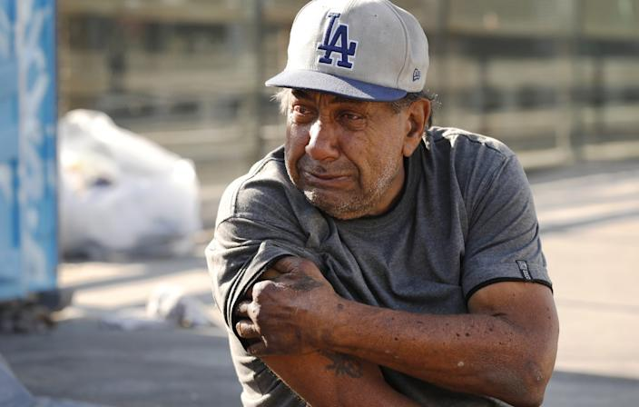 Eric Davido, who previously stayed in the El Puente shelter, sits outside his tent on a bridge over the 101 Freeway.
