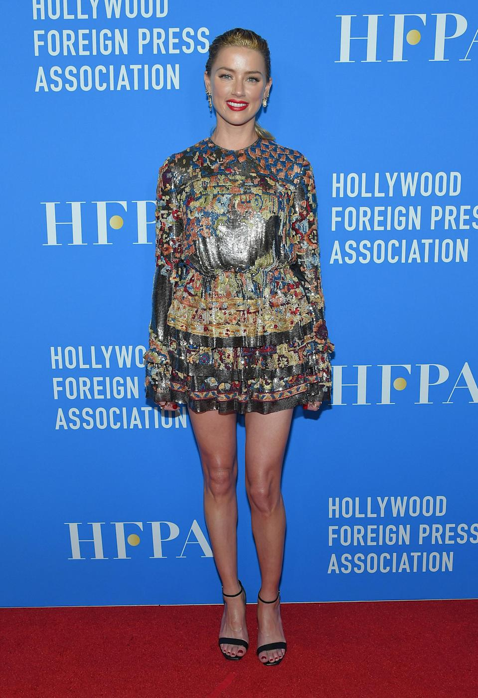 <p>Amber picked out a printed, mini Saint Laurent dress for a red carpet appearance this month. <em>[Photo: Getty]</em> </p>