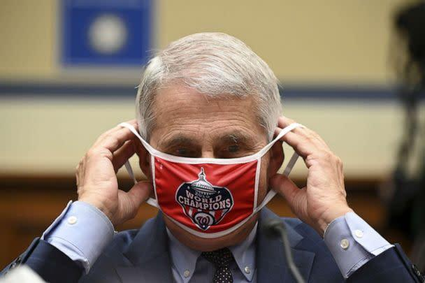 PHOTO: Anthony Fauci, director of the National Institute of Allergy and Infectious Diseases, removes his Washington Nationals protective mask during a House Select Subcommittee on the Coronavirus Crisis hearing on July 31, 2020, in Washington, D.C. (Pool/Getty Images)