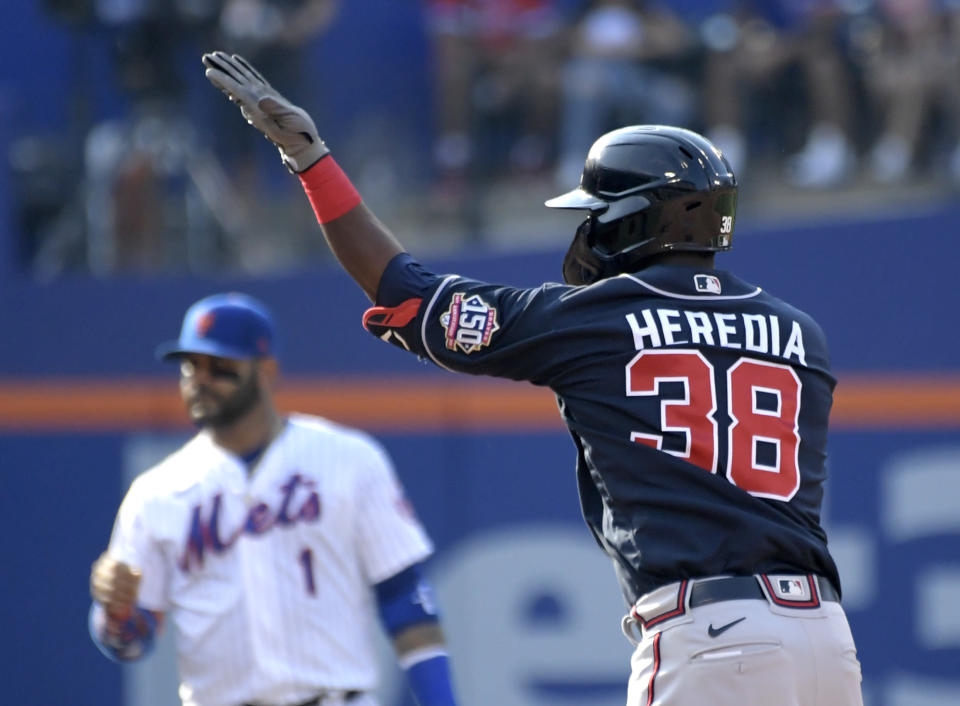 Atlanta Braves' Guillermo Heredia (38) signals to the dugout after hitting a double during the third inning of the first game of a baseball doubleheader against the New York Mets, Monday, July 26, 2021, in New York. (AP Photo/Bill Kostroun)