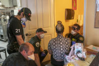 Salem Fire Department paramedics treat a restaurant worker who collapsed from heat exposure, in the back room of a restaurant during a heat wave, Saturday, June 26, 2021, in Salem, Ore. (AP Photo/Nathan Howard)