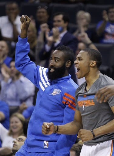 Oklahoma City Thunder guard James Harden, left, and guard Russell Westbrook, right, react to a teammate's basket in the second quarter of a preseason NBA basketball game against the Charlotte Bobcats in Oklahoma City, Tuesday, Oct. 16, 2012. (AP Photo/Sue Ogrocki)