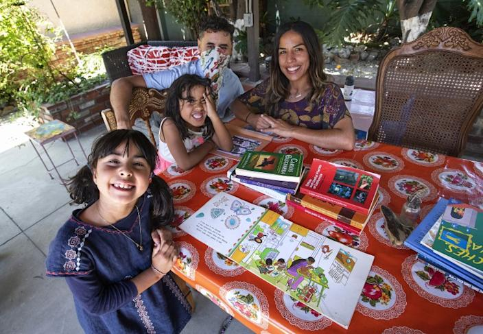 "Luna Tringale, 6, sister Anaya Tringale, 5, father Rolando Tringale and mother Kamren Curiel are preparing for school to resume next month. <span class=""copyright"">(Mel Melcon / Los Angeles Times)</span>"