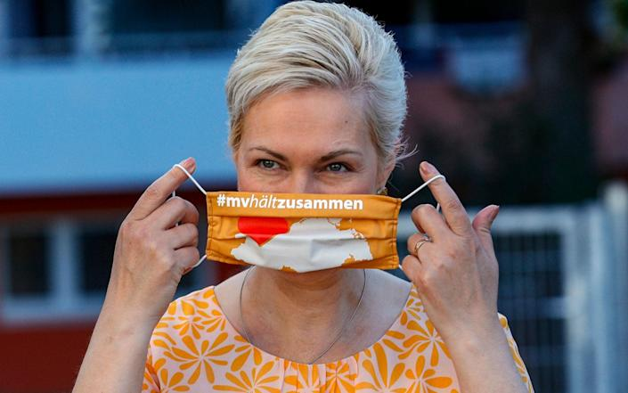 Mandatory Credit: Photo by FELIPE TRUEBA/EPA-EFE/Shutterstock (10729924d) Prime Minister of the German federal state of Mecklenburg-Western Pomerania, Manuela Schwesig, puts on a sanitary mask as she arrives at the Lankow elementary school enrolment ceremony in Schwerin, Germany, 01 August 2020. Thousands of children of Mecklenburg-Western Pomerania celebrated their first day in school with classes resuming on 03 August. This federal state is the first in Germany to officially open the new school year complying with health protocols imposed by the coronavirus pandemic. Children have to wear mask in the common areas of the school buildings. First day in school for pupils of Mecklenburg-Western Pomerania, Schwerin, Germany - 01 Aug 2020 - FELIPE TRUEBA/EPA-EFE/Shutterstock