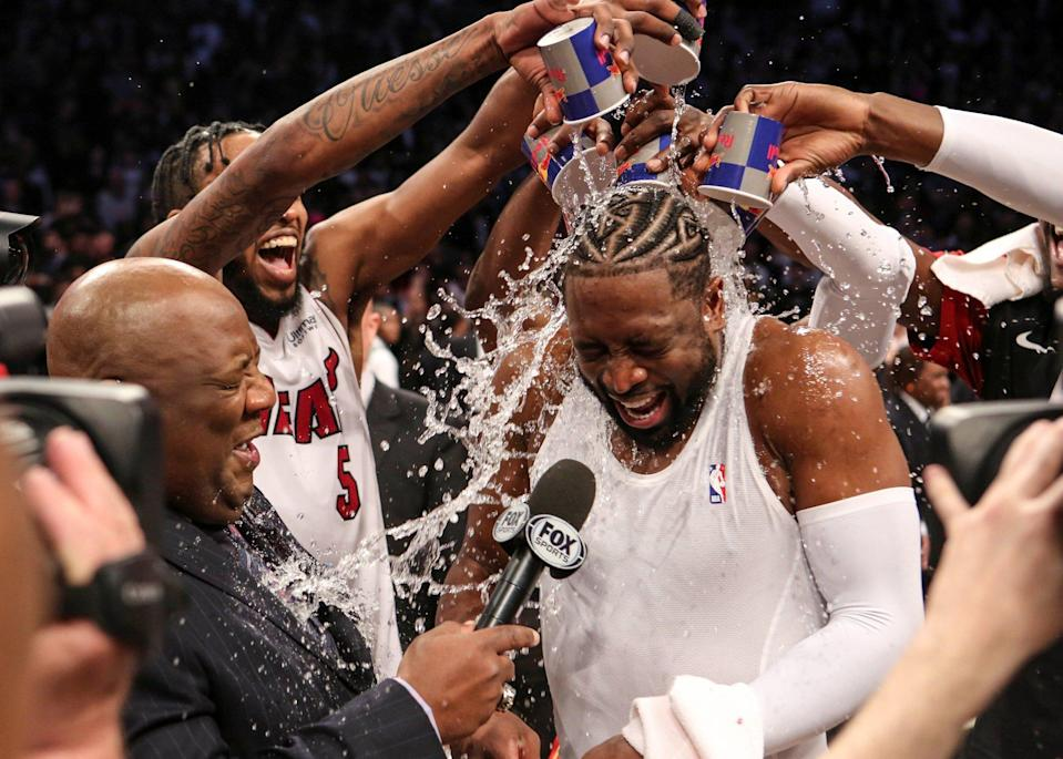 Ex-Miami Heat guard Dwyane Wade is doused with water from his teammates after playing his last NBA game against the Brooklyn Nets in April 2019: Photo: USA Today