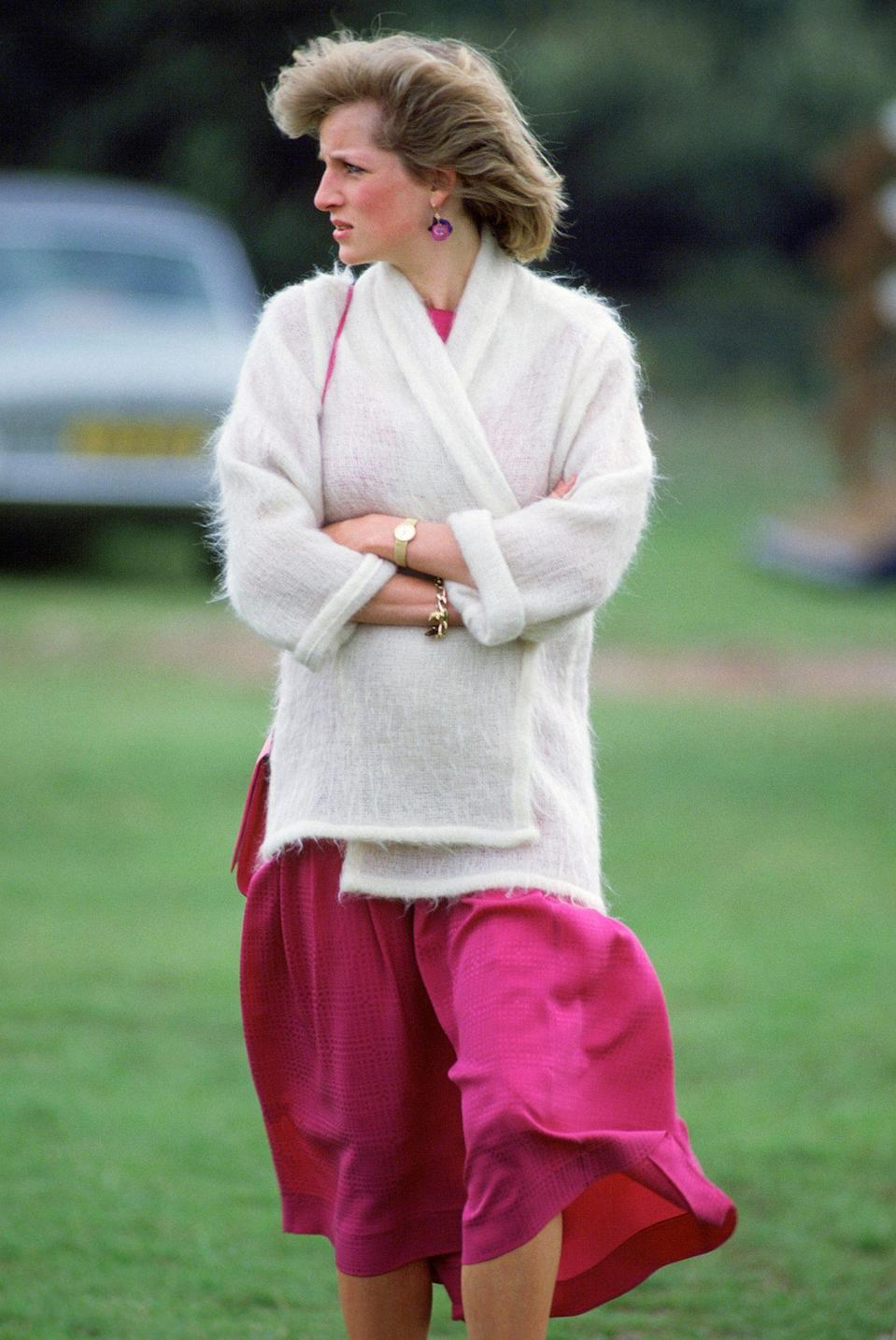 <p>The royal wrapped up in a white cardigan sans buttons over a pink dress for a 1984 polo match.</p>