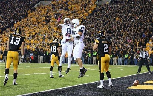 Penn State wide receiver Allen Robinson (8) and tight end Jesse James (18) celebrate James' first-quarter touchdown as Iowa linebacker Tom Donatell (13), Iowa cornerback Micah Hyde (18) and Iowa defensive back Greg Castillo (2) walk off the field during the first half of their NCAA college football game against Iowa at Kinnick Stadium in Iowa City, Iowa, Saturday, Oct. 20, 2012. (AP Photo/Justin Hayworth)