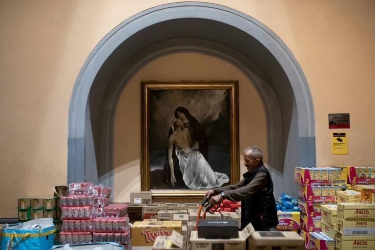 A volunteer prepares rations of donated food at Santa Anna church in Barcelona. Spain is struggling to cope with an avalanche of applications for its minimum basic income scheme