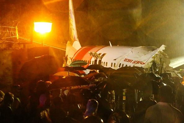 First responders gather around the wreckage of an Air India Express jet, which was carrying more than 190 passengers and crew from Dubai, after it crashed by overshooting the runway at Calicut International Airport in Karipur, Kerala.