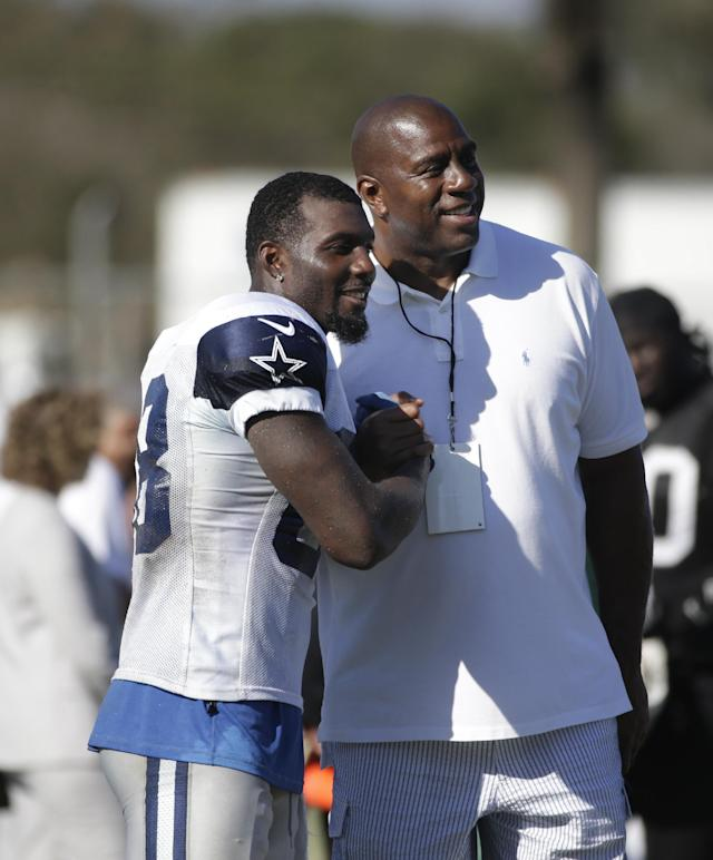 Dallas Cowboys wide receiver Dez Bryant, left, and Los Angeles Dodgers part-owner Magic Johnson pause for photos during the team's joint football practice with the Oakland Raiders on Tuesday, Aug. 12, 2014, in Oxnard, Calif. (AP Photo/Jae C. Hong)