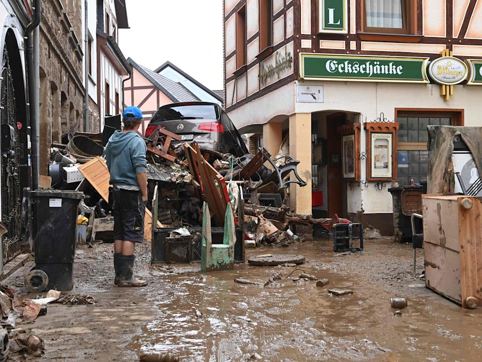 A local resident stands next to debris and a damaged car in a street in Bad Neuenahr-Ahrweiler, western Germany, (AFP via Getty Images)