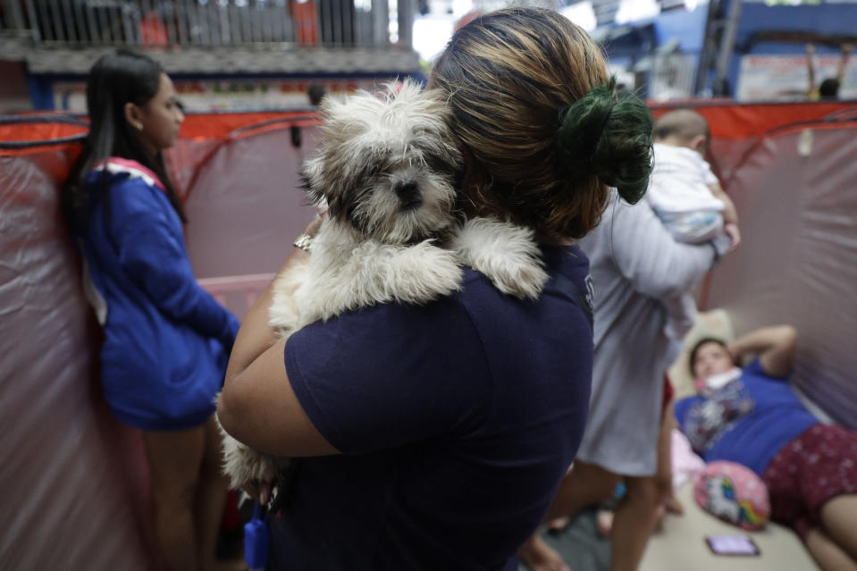 A resident carries her dog inside an evacuation center as rains from a typhoon locally known as Goni start to pour in Manila, Philippines on Sunday, Nov. 1, 2020. A super typhoon slammed into the eastern Philippines with ferocious winds early Sunday and about a million people have been evacuated in its projected path, including in the capital where the main international airport was ordered closed. (AP Photo/Aaron Favila)