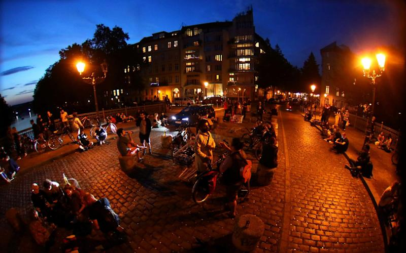 People sit after sunset at the admiral bridge, a popular meeting point for tourists and residents, amid the coronavirus outbreak - REUTERS/Hannibal Hanschke