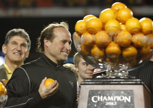 West Virginia's head coach Dana Holgorsen holds an orange following their victory in the Orange Bowl NCAA college football game, Wednesday, Jan. 4, 2012, in Miami. West Virginia defeated Clemson 70-33. (AP Photo/Lynne Sladky)