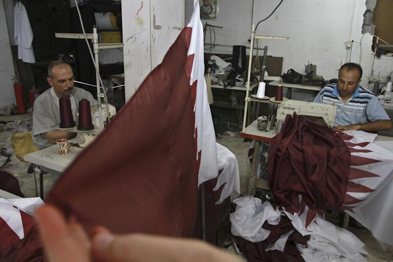 Palestinian tailors Eyad Absi, left and Salama Ashour make Qatari flags in a shop for Tuesday's official visit of the Emir of Qatar Sheikh Hamad bin Khalifa al-Thani in Gaza City, Sunday, Oct. 21, 2012. (AP Photo/Adel Hana)