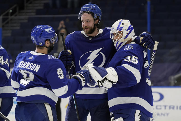 Tampa Bay Lightning goaltender Curtis McElhinney (35) celebrates with defenseman Victor Hedman (77) and center Tyler Johnson (9) after the team defeated the Florida Panthers during an NHL hockey game Sunday, March 21, 2021, in Tampa, Fla. (AP Photo/Chris O'Meara)