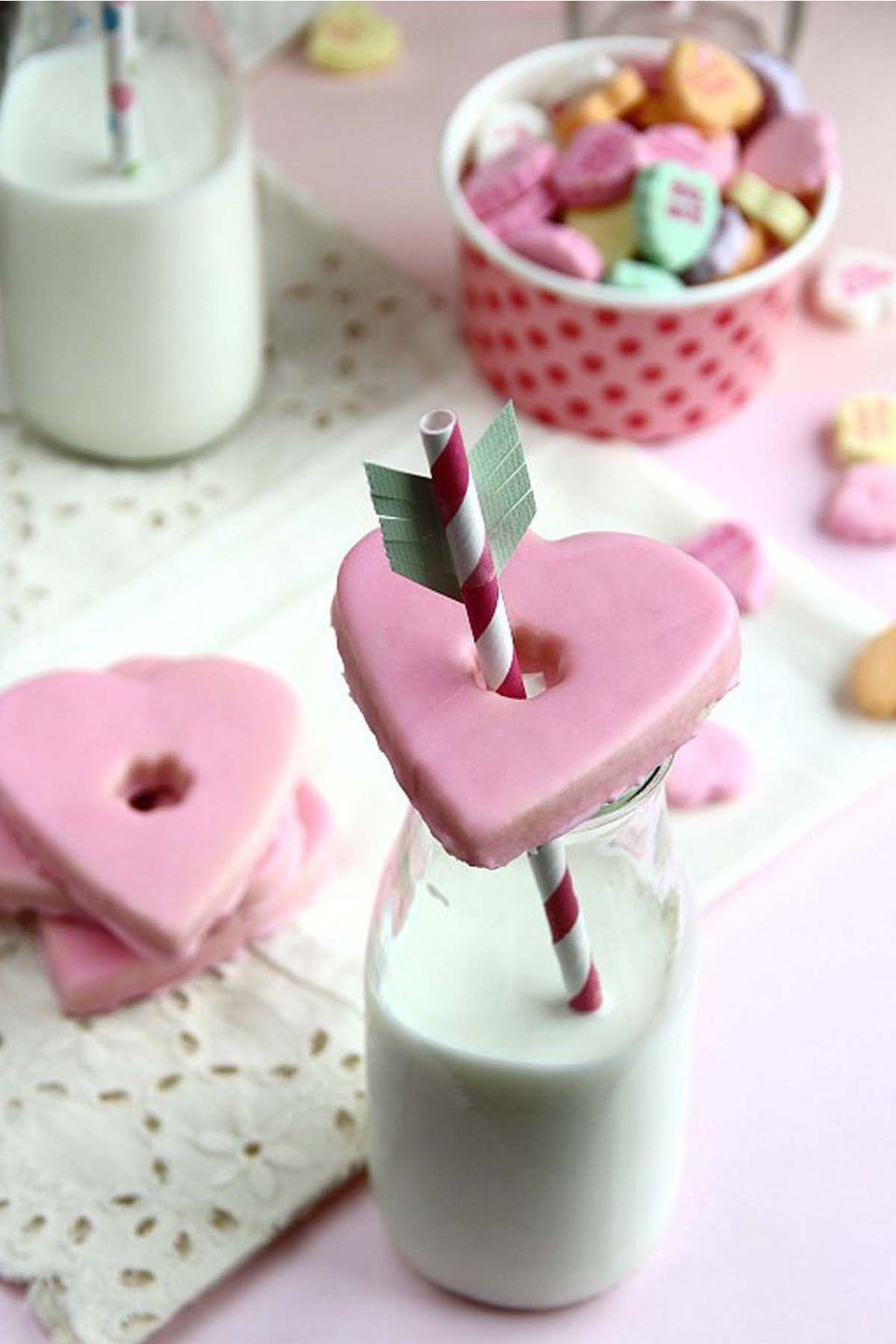 "<p>Upgrade plain old milk and cookies with this on-target idea. Using a small fondant cutter or paring knife, create a hole in a heart-shaped cookie (store-bought is fine). Place the cookie on top of a milk glass, then insert a paper straw ""arrow"" embellished with construction paper fringe.</p><p><strong>Get the recipe at <a href=""http://cookiesandcups.com/glass-topper-valentines-cookies/"" rel=""nofollow noopener"" target=""_blank"" data-ylk=""slk:Cookies and Cups"" class=""link rapid-noclick-resp"">Cookies and Cups</a>. </strong></p>"