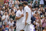 Russia's Daniil Medvedev shakes hands with Spain's Carlos Alcaraz, left, after winning the men's singles second round match on day four of the Wimbledon Tennis Championships in London, Thursday July 1, 2021. (AP Photo/Kirsty Wigglesworth)