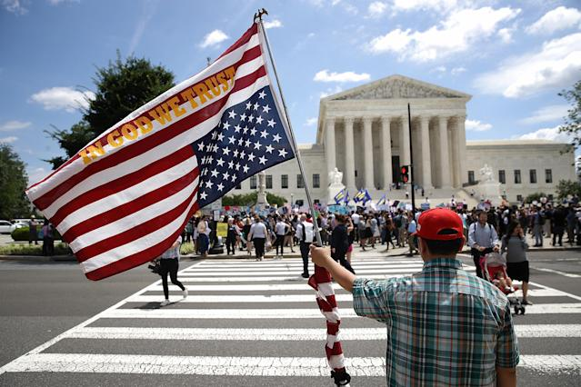 <p>A man bearing an upside down American flag watches as protesters gather outside the U.S. Supreme Court as the court issued an immigration ruling June 26, 2018 in Washington, D.C. (Photo by Win McNamee/Getty Images) </p>